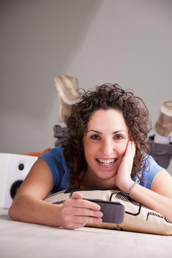 Muchacha sonriente que juega videojuegos en su móvil fotografía de archivo libre de regalías