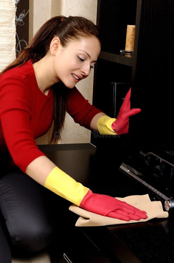 Muchacha sonriente que limpia la casa fotos de archivo