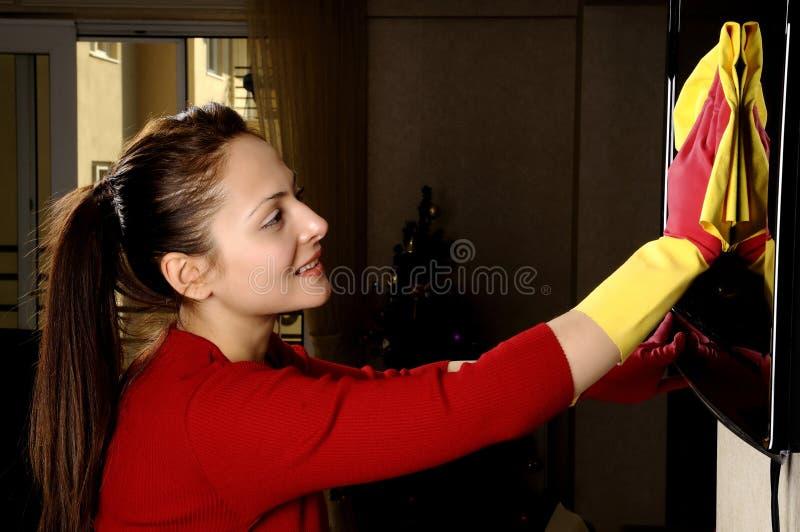 Muchacha sonriente que limpia la casa foto de archivo
