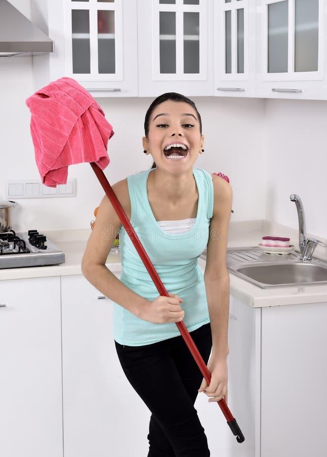 Muchacha sonriente que limpia la casa imagenes de archivo