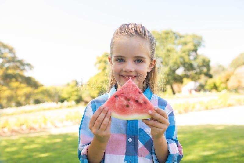 Muchacha sonriente que lleva a cabo la rebanada de la sandía en el parque fotos de archivo