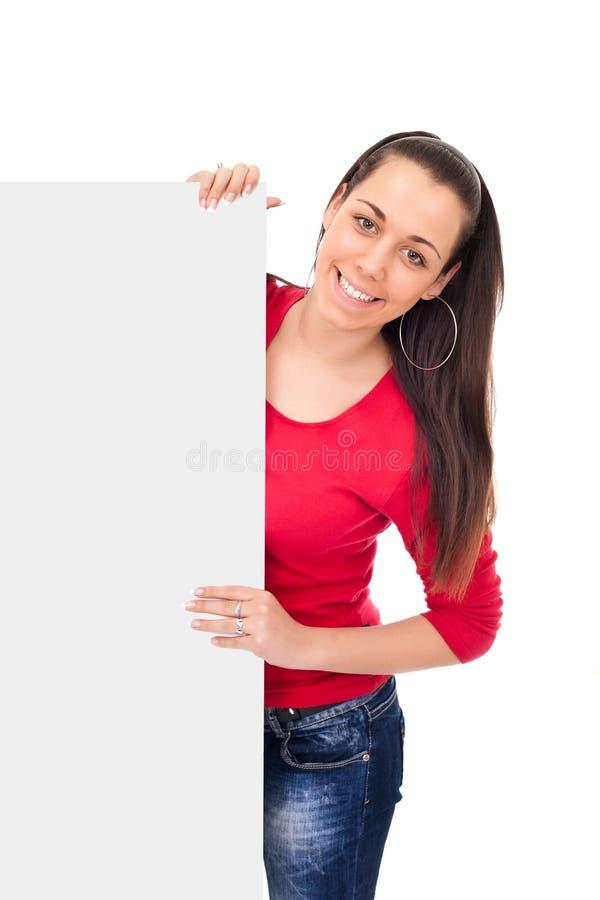 Muchacha sonriente que lleva a cabo a la tarjeta en blanco imagenes de archivo