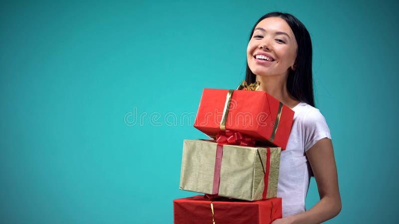 Muchacha sonriente que lleva a cabo muchos giftboxes, presentes del fest, coloc?ndose en fondo azul fotografía de archivo