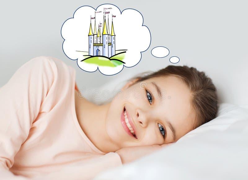 Muchacha sonriente que miente en cama y que sueña con castillo imágenes de archivo libres de regalías