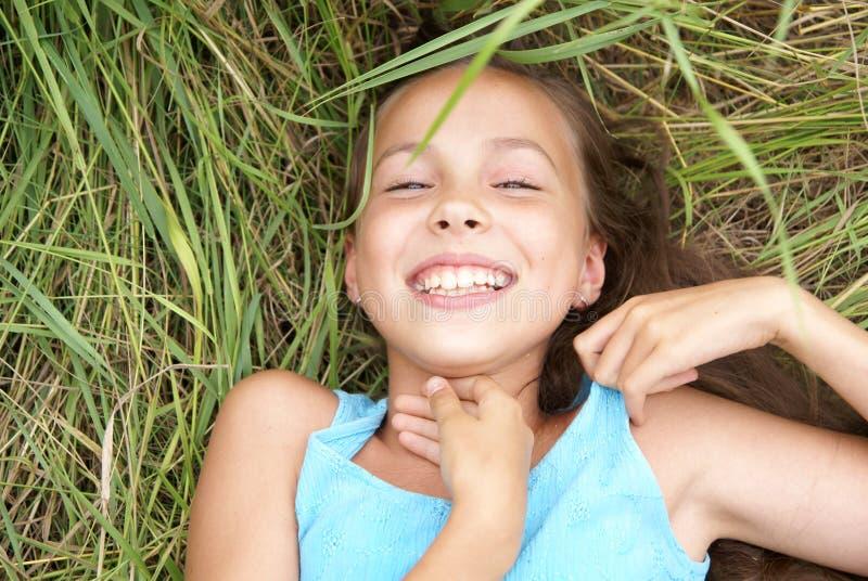 Muchacha sonriente que miente en hierba imágenes de archivo libres de regalías