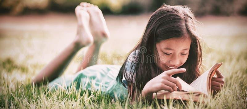 Muchacha sonriente que miente en hierba y el libro de lectura en parque imagenes de archivo