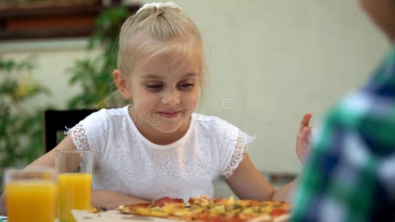 Muchacha sonriente que mira con amor la pizza sabrosa en el restaurante al aire libre, apetito fotografía de archivo
