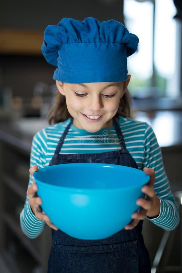 Muchacha sonriente que mira en el cuenco en la cocina imagenes de archivo