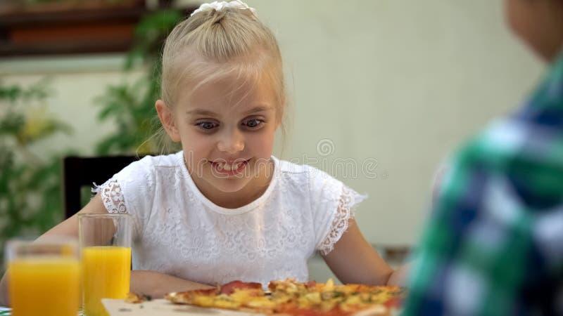 Muchacha sonriente que mira la pizza y elegir la mejor rebanada, tradiciones de la comida de la familia imagenes de archivo