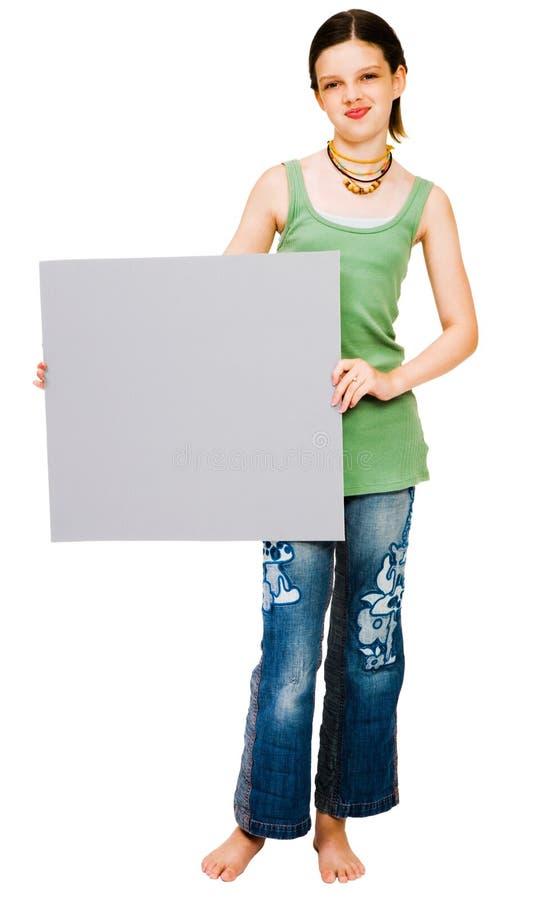 Muchacha sonriente que muestra el cartel imagen de archivo libre de regalías