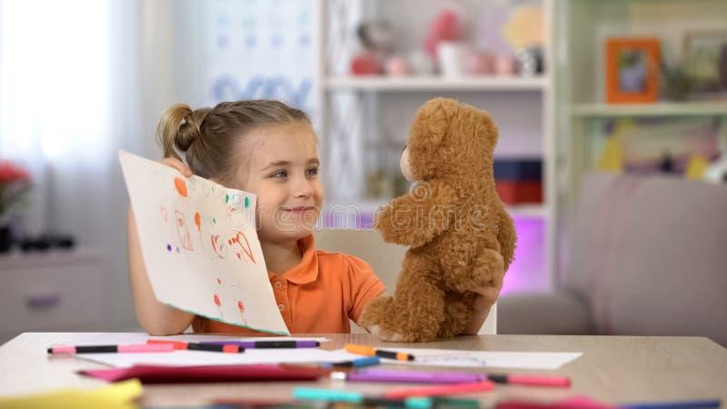 Muchacha sonriente que muestra el oso de peluche de los dibujos, ocio de la sala de juegos, amigo imaginario foto de archivo