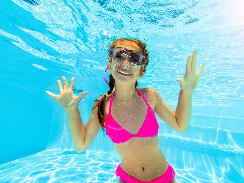 Muchacha sonriente que nada bajo el agua en piscina imagenes de archivo