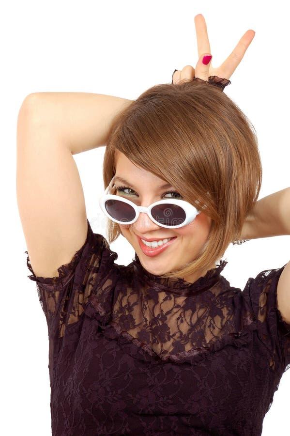 Muchacha sonriente que presenta con los claxones del dedo fotos de archivo libres de regalías