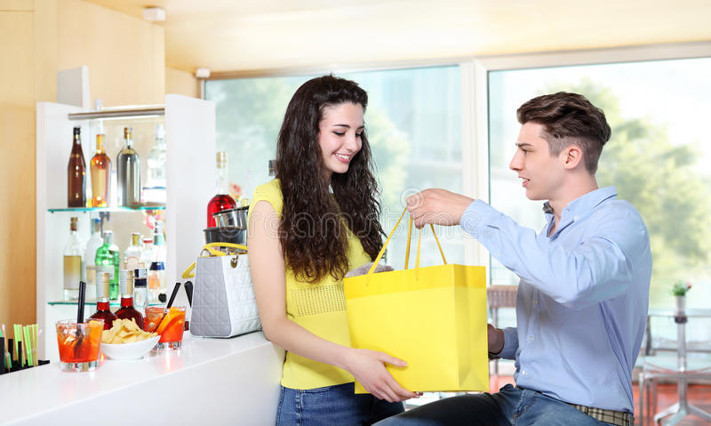 Muchacha sonriente que recibe un regalo de su novio foto de archivo libre de regalías