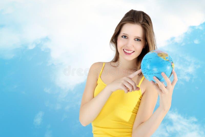 Muchacha sonriente que señala al mapa del mundo imagenes de archivo