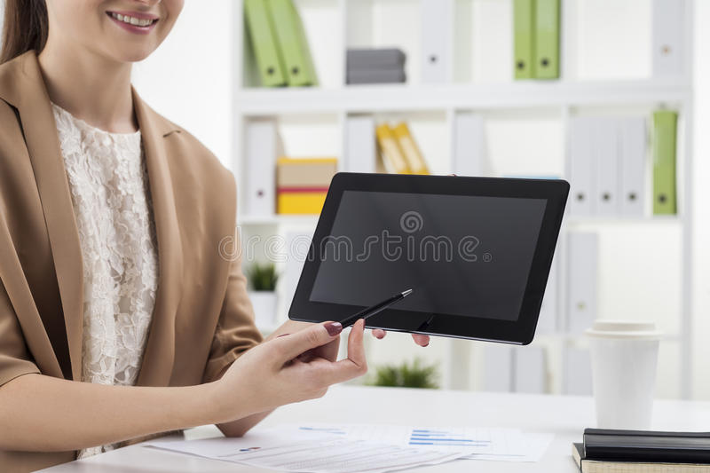 Muchacha sonriente que señala en la pantalla de tableta en oficina fotos de archivo libres de regalías