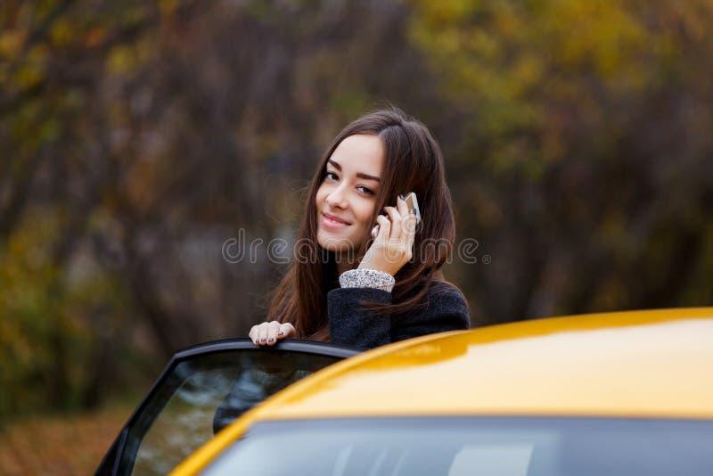 Muchacha sonriente que se coloca cerca del coche y que habla en el teléfono foto de archivo