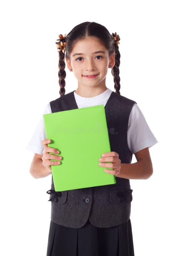 Muchacha sonriente que se coloca con el libro imagen de archivo