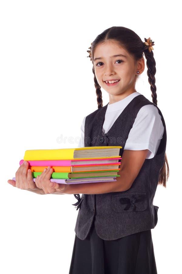 Muchacha sonriente que se coloca con la pila de libros fotografía de archivo libre de regalías