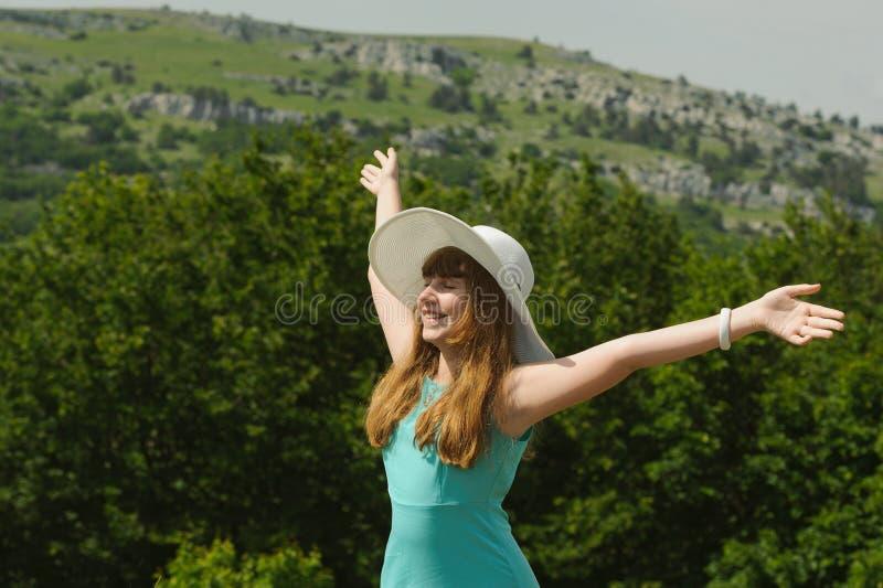 Muchacha sonriente que se coloca con los brazos extendidos contra backg verde imagenes de archivo