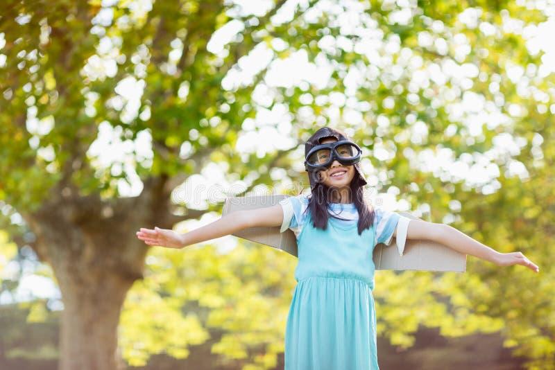 Muchacha sonriente que se coloca con los brazos extendidos en parque foto de archivo libre de regalías