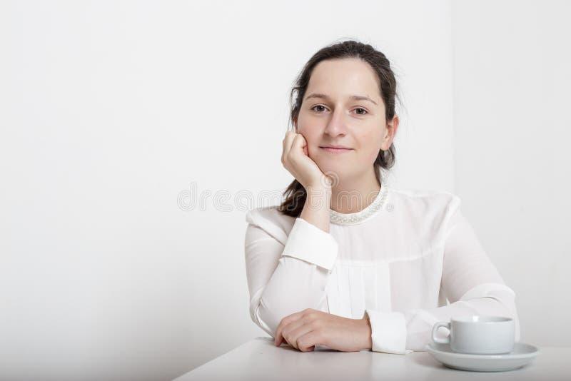 Muchacha sonriente que se sienta en el café en la tabla, en la cual coloca a foto de archivo