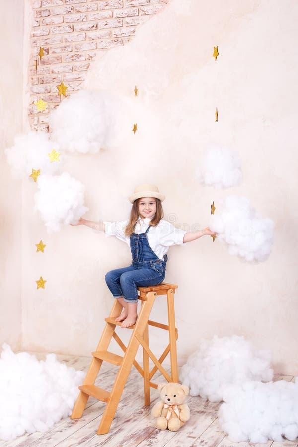 Muchacha sonriente que se sienta en las escaleras en el cielo con las nubes y con las estrellas Peque?o viajero de Little del ast fotos de archivo libres de regalías