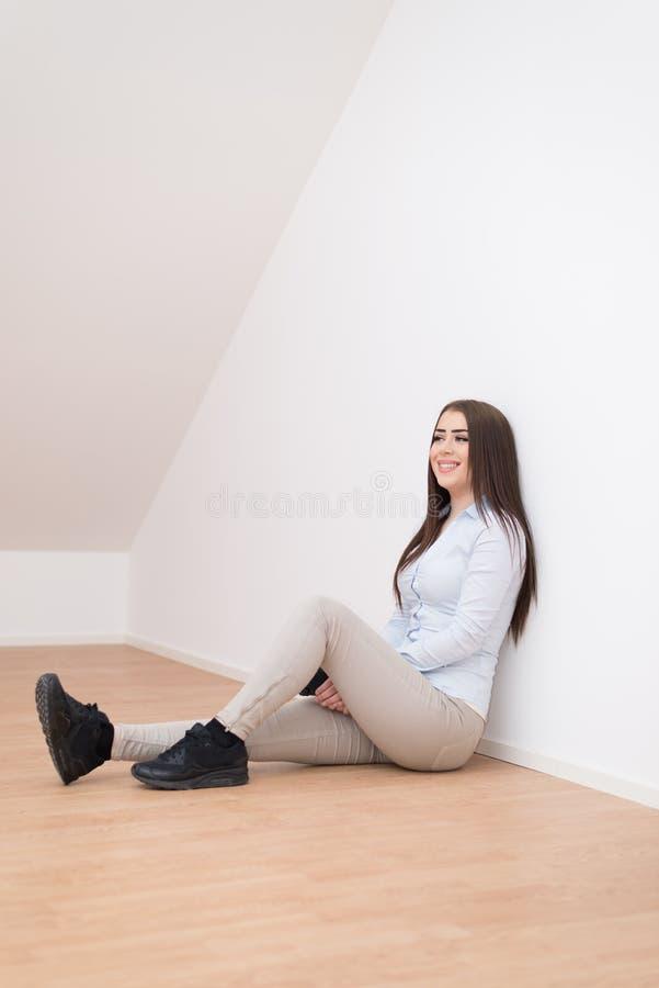 Muchacha sonriente que se sienta en piso fotos de archivo libres de regalías