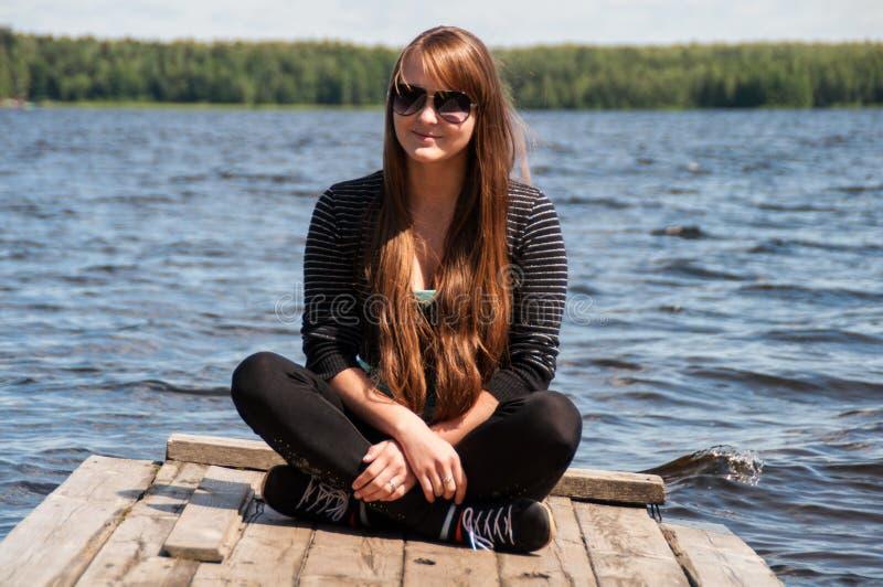 Muchacha sonriente que se sienta en un embarcadero imágenes de archivo libres de regalías