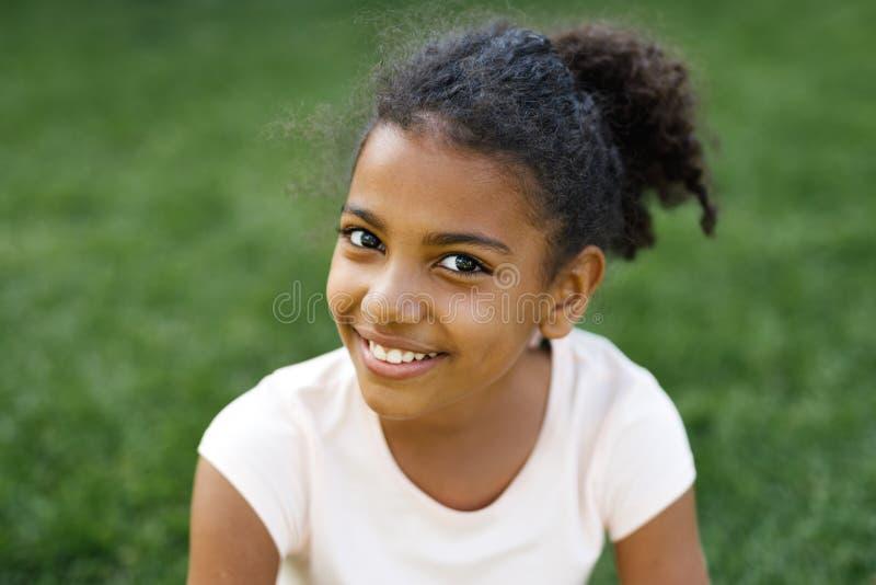 Muchacha sonriente que se sienta en una hierba en parque foto de archivo