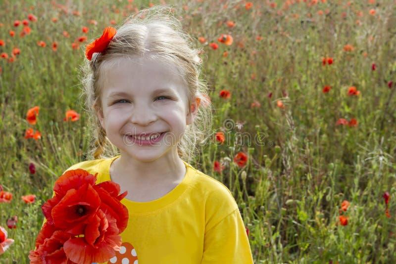 Muchacha sonriente que sostiene amapolas del ramo foto de archivo