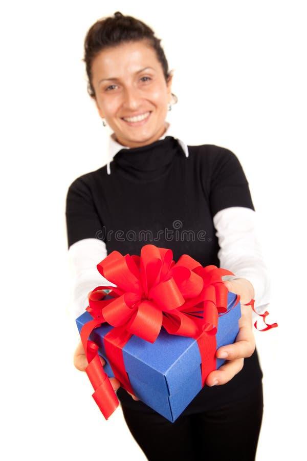 Muchacha sonriente que sostiene la caja de regalo azul con la cinta roja foto de archivo
