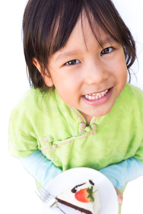 Muchacha sonriente que sostiene la torta de chocolate en la placa blanca Cara feliz imagenes de archivo