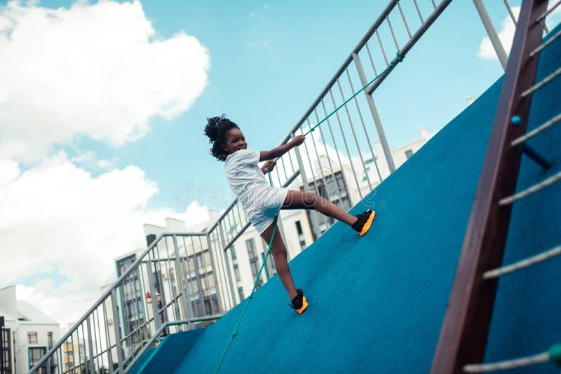 Muchacha sonriente que sube para arriba en una tierra de deportes imagen de archivo