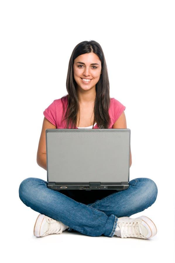 Muchacha sonriente que trabaja en la computadora portátil imagenes de archivo