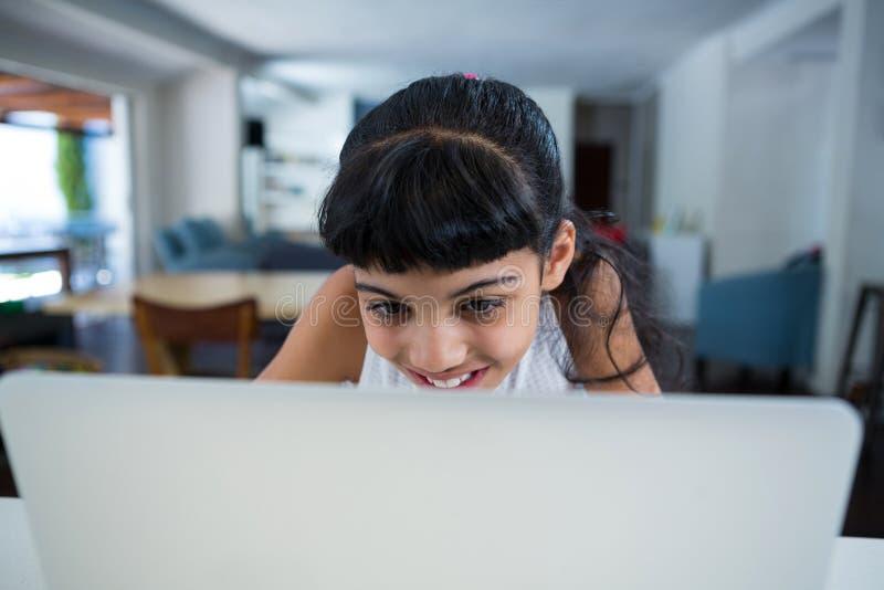 Muchacha sonriente que usa la computadora portátil imagenes de archivo