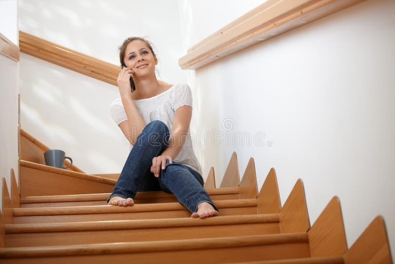 Muchacha sonriente que usa la sentada móvil en las escaleras foto de archivo libre de regalías