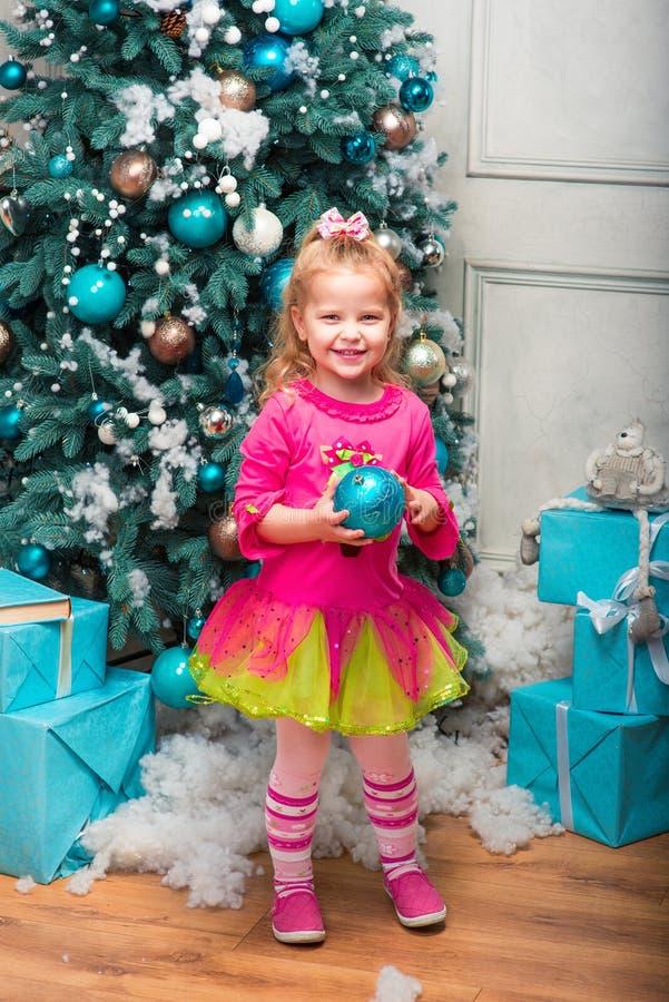 Muchacha sonriente rubia poco bastante rizada que coloca casi el árbol de navidad foto de archivo