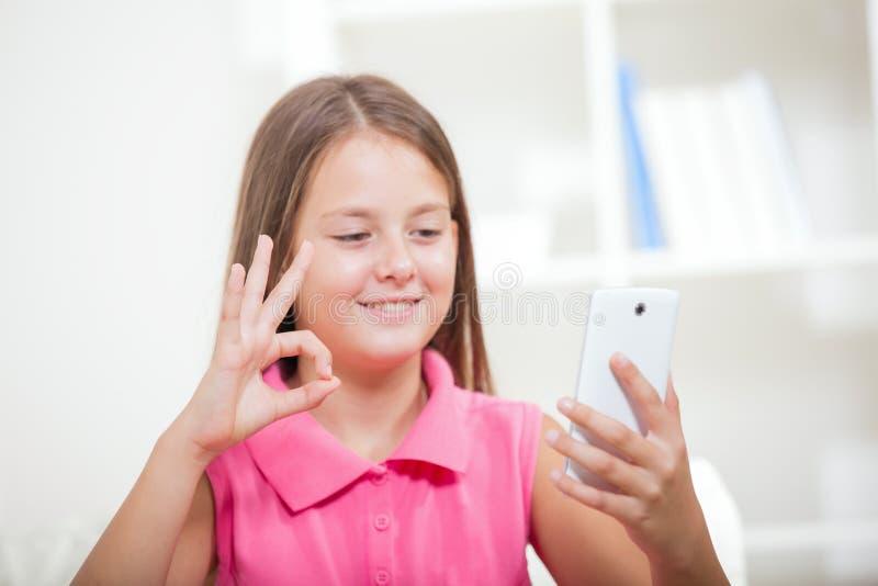 Muchacha sorda que habla usando lenguaje de signos en la leva del smartphone fotografía de archivo
