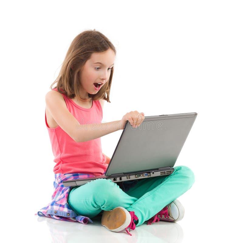 Muchacha sorprendida con un ordenador portátil fotografía de archivo