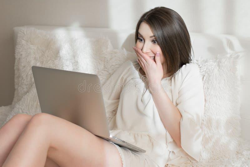 Muchacha sorprendida con un ordenador portátil en la cama imagenes de archivo