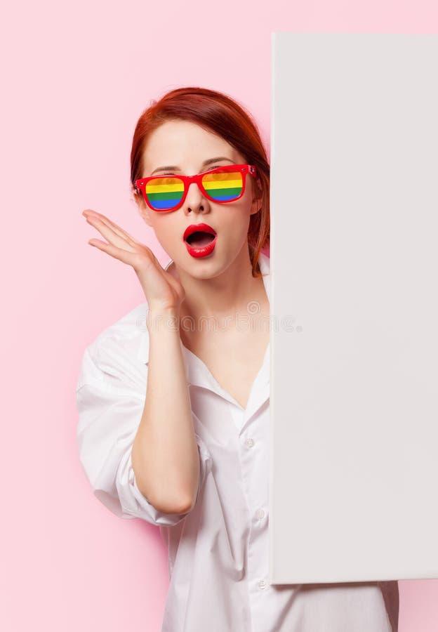 Muchacha sorprendida del estudiante en la camisa y los vidrios blancos imagen de archivo