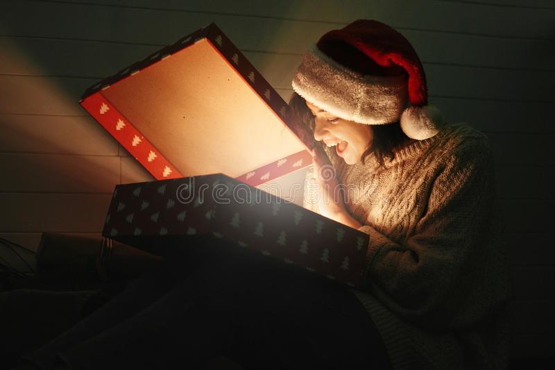 Muchacha sorprendida elegante en el sombrero de santa y la caja de regalo de apertura de la Navidad del suéter acogedor con la lu imagen de archivo libre de regalías