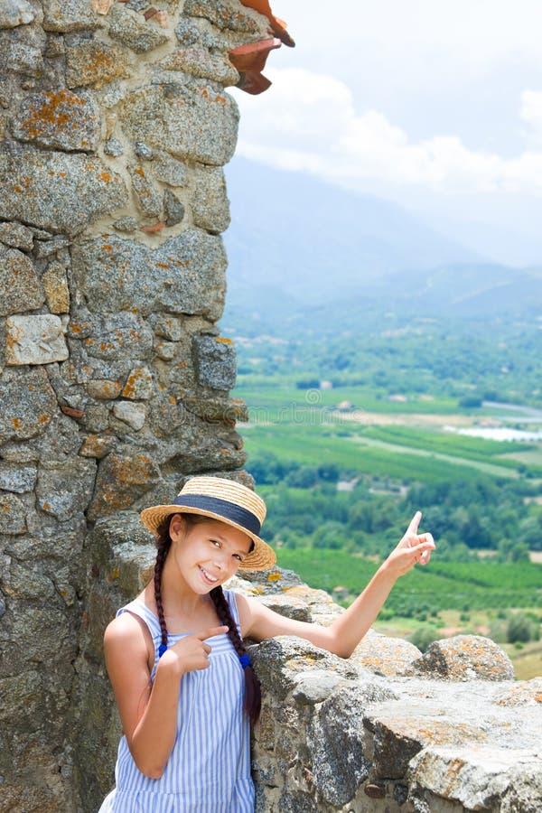 Muchacha sorprendida en sombrero de paja cerca de la pared antigua en Eus, Francia fotografía de archivo libre de regalías