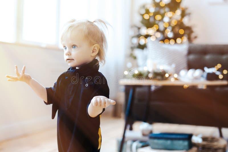 Muchacha sorprendida niño lindo en sala de estar El árbol de navidad está en fondo imagen de archivo