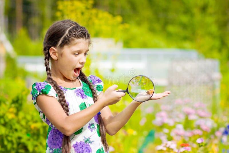 Muchacha sorprendida que mira a través de la lupa en la flor con el escarabajo imagenes de archivo