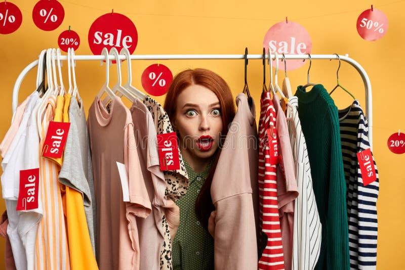 Muchacha sorprendida que oculta detrás de la ropa foto de archivo libre de regalías