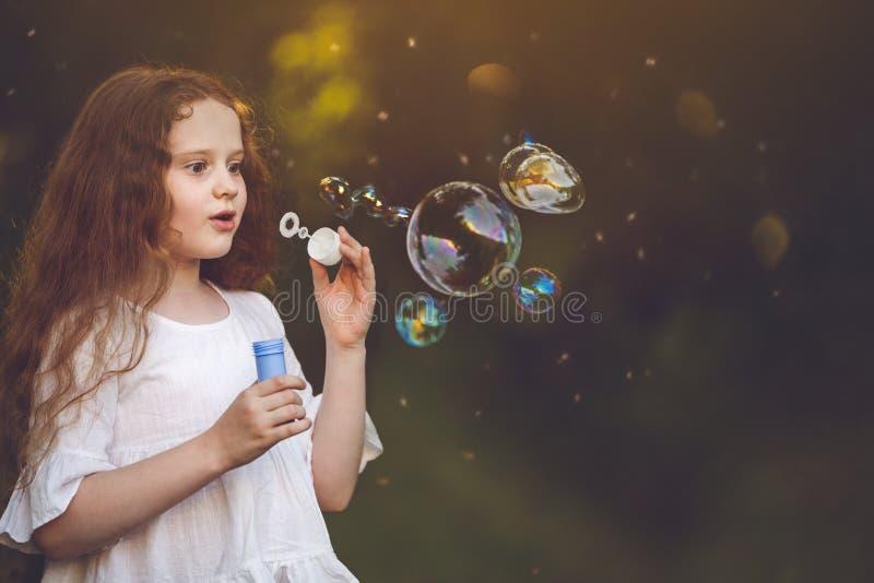Muchacha sorprendida que sopla hacia fuera una burbuja de jabón fotografía de archivo libre de regalías