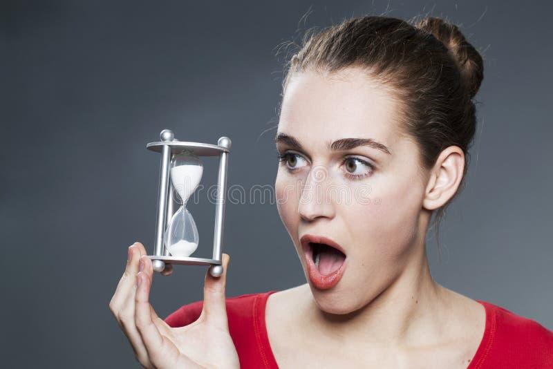 Muchacha sorprendida 20s con el símbolo del tiempo y de los plazos foto de archivo