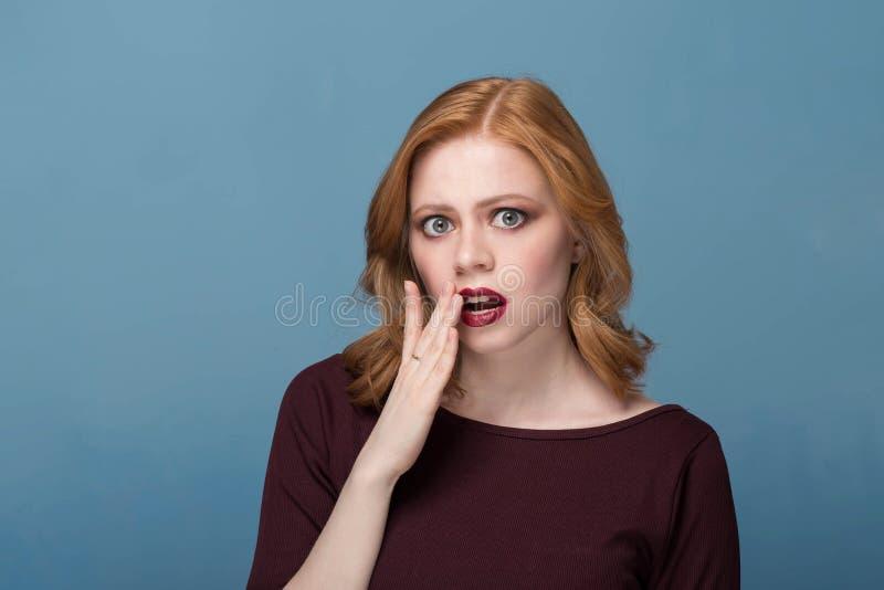 Muchacha sorprendida y chocada hermosa con el pelo rizado Una mujer joven con maquillaje brillante en un fondo azul imagenes de archivo